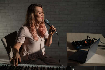 A young European woman sings into a microphone and accompanies on an electronic piano. The girl shoots a video blog. Remote vocal lesson. A female singing teacher conducts online classes. Foto de archivo
