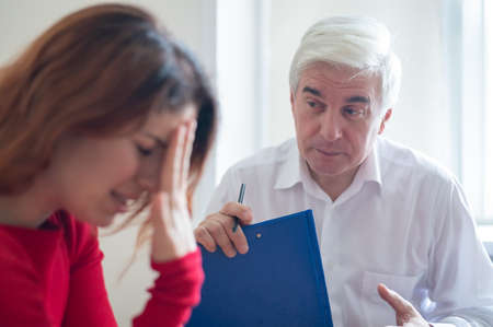 A frustrated crying woman holds palms in her face at a session with a male psychologist. Mature gray-haired psychotherapist talking to a female patient with depression and neurosis. Unbalanced psyche. Foto de archivo