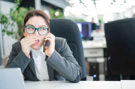 A woman sits in an office at her desk and gossips on the phone. Corporate ethics. Female employee in a suit tells secrets on a smartphone at work. Foto de archivo