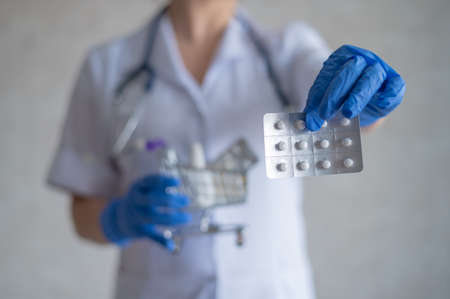 A faceless female doctor in rubber gloves shows a blister with pills and holds a mini shopping cart with a full pack of different medicines. Pharmacist recommendations. Foto de archivo
