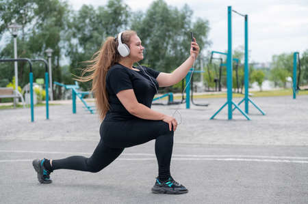 A beautiful fat girl in headphones is engaged in fitness on the sports ground and takes a selfie. Young woman lunges and is photographed on a smartphone outdoors on a warm summer day.