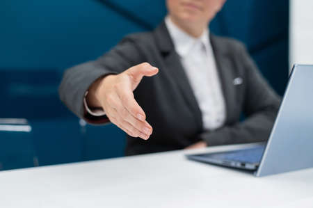 Faceless woman in a business suit holds out her hand for a handshake while sitting at a desk. Female boss makes a successful deal.