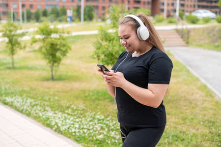 A beautiful fat girl in black sportswear listens to music on headphones and text messages on the phone while walking outdoors. A plump young woman is leafing through a music playlist in smartphone.