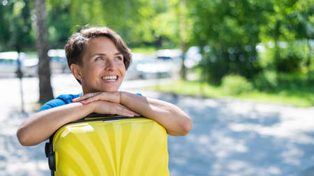 Close-up portrait of a beautiful short-haired Caucasian young woman with a yellow suitcase outdoors. The girl with a perfect smile dreamily leaned her head against a large luggage bag.