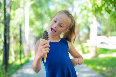 Happy little caucasian girl in blue dress eats chocolate ice cream cone outdoors. An emotional excited child enjoys a cooling gelato on a hot summer day.