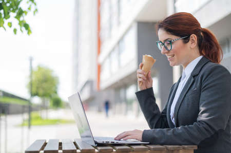 Happy woman works at a computer while sitting on a summer terrace of a cafe and eating vanilla ice cream. Female employee is typing on a laptop keyboard and holding an ice cream cone. Cooling dessert.