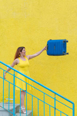 A happy red-haired woman in a yellow dress is walking down the stairs and joyfully swing a blue suitcase. The girl is preparing for the journey. Summer vacation concept. Foto de archivo