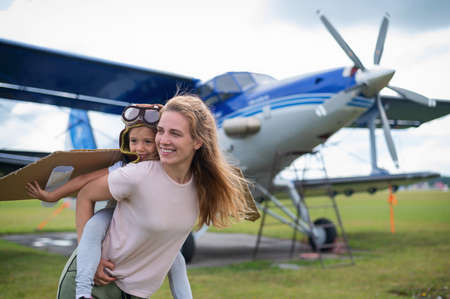 Beautiful caucasian woman is holding her little daughter at the airfield. A small girl in a pilots costume sits on her mothers back against the background of the plane.