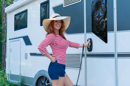 A beautiful red-haired woman in a hat stands at a white mobile home. A smiling girl in a striped jacket opens the door to the Caravan for life and family road trips.