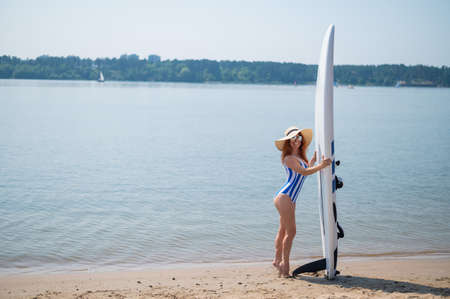 A beautiful red-haired woman in a straw hat, sunglasses and a striped one-piece swimsuit stands on the beach and holds a sup board. Happy smiling girl surfing on the lake.