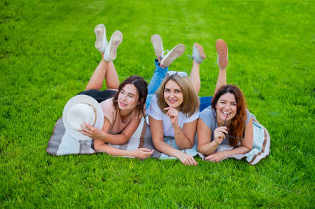 Three beautiful Caucasian young women are lying on the lawn. The blonde brunette and the redhead are resting in the park on the green grass. The friends had an outdoor picnic.