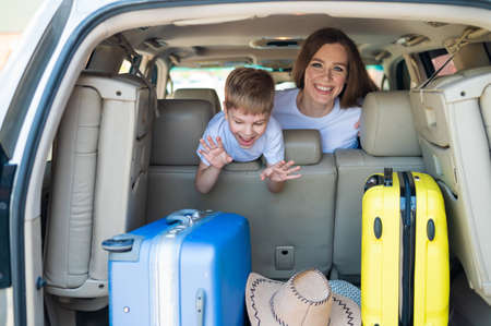 Happy European woman with her little son look back at the trunk of a car with suitcases. Family summer vacation. Traveling by car with a child. A boy with his mother in the back seat of a car.