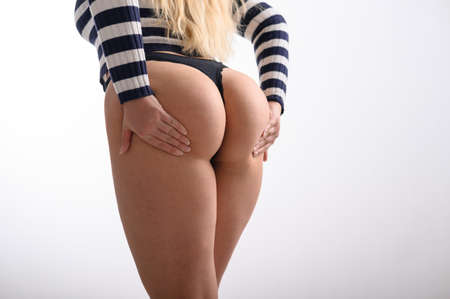A blonde with long hair stands against a white wall and holds her hands on her buttocks. Rear view of a girl in thongs and a striped sweater. A woman with wide hips, a big booty and a narrow waist.