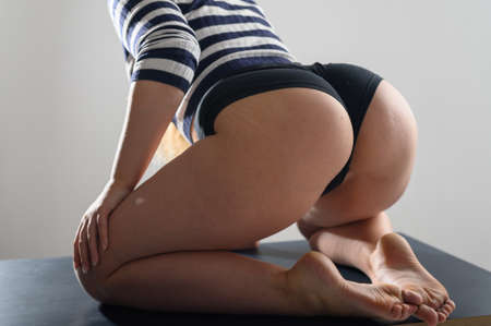 A girl with a big booty sits on a knitted blanket. A woman in a striped sweater and high-waisted denim shorts sits on her knees on a gray woolen carpet. Dancer Twerk. Close up.
