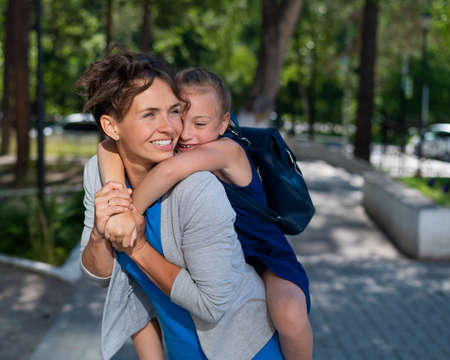 Beautiful caucasian woman holds her daughter schoolgirl on her back outdoors. A girl with a backpack lovingly hugs her mother from behind.