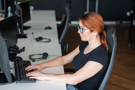Redhead woman in glasses and casual wear working overtime. Focused girl alone works on a computer in an empty office. Deadline. The IT specialist enthusiastically works on the weekend. Archivio Fotografico