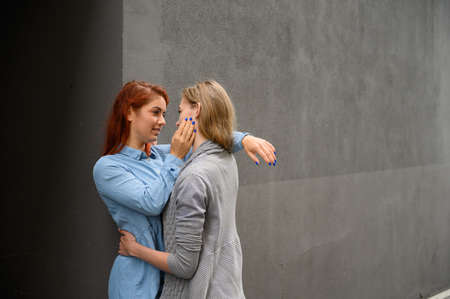 Passionate loving lesbian couple. Two beautiful young women hugging tenderly outdoors against a gray wall. LGBT commune. Girls on a date.