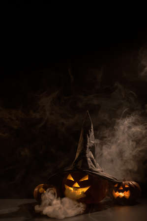 Vertical Halloween card. Witch hat on a pumpkin with carved creepy grimaces on a black background in the fog. Jack-o-lantern glows from the inside and emits smoke.