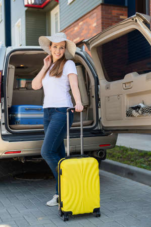 European woman in a hat alone packs her bags for a car trip. Beautiful happy girl loads a suitcase in the car trunk. Yellow luggage for summer holidays.