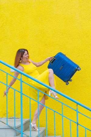 A happy red-haired woman in a yellow dress is walking down the stairs and joyfully swing a blue suitcase. The girl is preparing for the journey. Summer vacation concept. 版權商用圖片