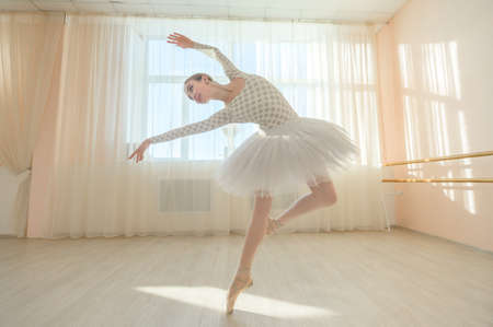 Beautiful graceful ballerina is practicing in the hall against the background of a window. Slender woman in tutu and pointe shoes in a dance class. 版權商用圖片