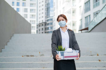 Unhappy fired masked woman is standing in the street with a box of personal items from the desktop. An unemployed desperate woman descends the stairs outside. Job cuts during the coronavirus epidemic.