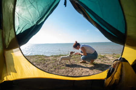 View from a tourist tent on a woman playing with a dog on the seashore. The girl set up camp in the countryside. 免版税图像