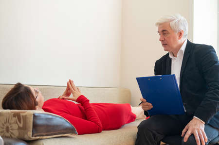 Close-up of a male psychotherapists hand writing on a clipboard. A woman in a red dress lies on a couch and talks about her problems to a psychologist at a session. Mental health.