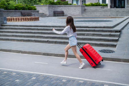 Happy beautiful caucasian woman is running with a big red suitcase outdoors. Excited girl is late for the plane.