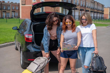Three friends are going on a road trip for the summer vacation and are looking at the map. Young women load suitcases into the trunk of a car. Reklamní fotografie