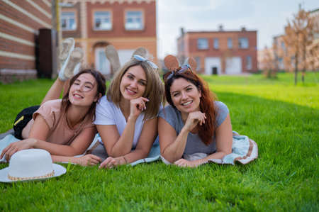Three beautiful Caucasian young women lie on the lawn in the countryside. The blonde brunette and the redhead are resting in the park on the green grass. The friends had an outdoor picnic. Reklamní fotografie