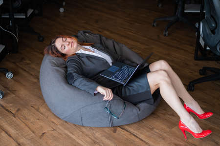 Modern advanced office. A woman in a business suit asleep in a beanbag while working on a laptop. Female manager is resting in a soft chair. Caring for the comfort of employees.