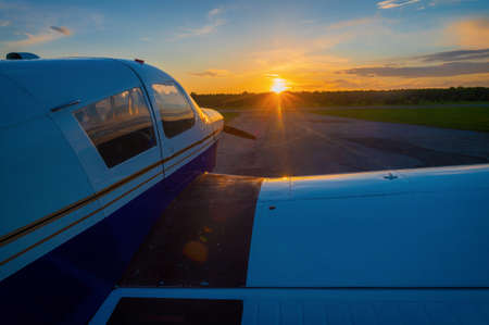 Close-up of a small parked plane with a propeller against the backdrop of a sunset.