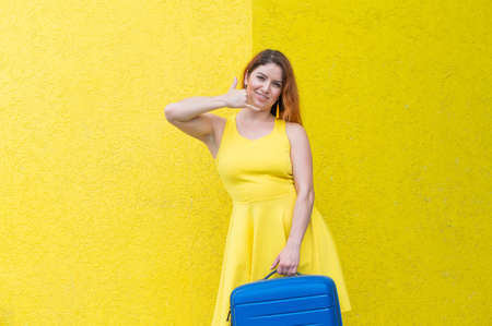 A beautiful red-haired woman in a dress holds a blue suitcase and gestures a phone call on a yellow background. 스톡 콘텐츠