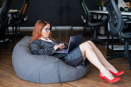 Modern open space office. A woman in a business suit and red high heels sitting in the beanbag and typing on laptop. Female manager is working in a soft chair. Caring for the comfort of employees.