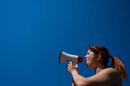 Red-haired Caucasian woman yelling into a megaphone against a blue sky background. The girl makes an announcement through the loudspeaker.