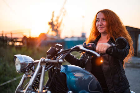 Curly red-haired woman in a black leather jacket sits on a motorcycle at sunset. Portrait of a serious girl driving a bike. Banque d'images