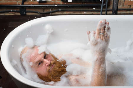 Close-up portrait of funny red-bearded bald man taking a bath with foam. Cheerful naughty guy at spa treatments. A parody of glamorous girls.