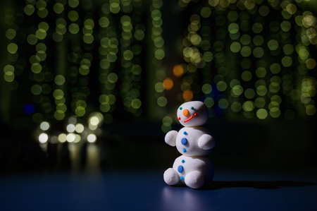 Cute snowman and little trees made of marshmallows on the background of fairy lights. White mug of hot chocolate and sweets. Stock Photo