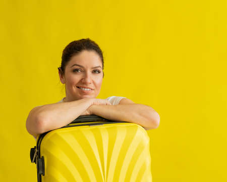 Portrait of a beautiful caucasian woman with a suitcase dreaming of vacation on a yellow background. A smiling girl leaned on her luggage bag. Banque d'images