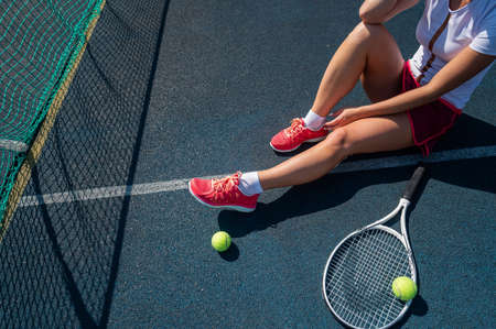 A faceless girl in a sports skirt sits on a tennis court and holds a rocket. Top view of female legs. Zdjęcie Seryjne