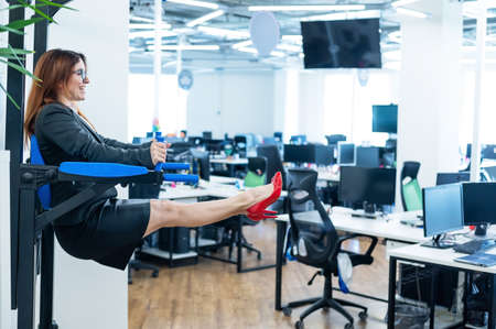 Business woman doing exercises on the mounted horizontal bar in the office. Sports during a break at work.