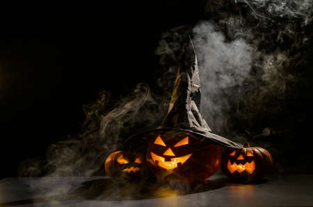 Three jack o lanterns glow in the dark amidst the fog. Halloween pumpkin in a witch hat.