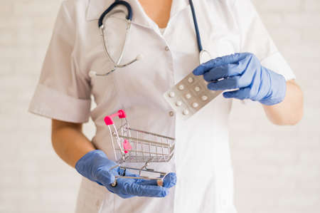 A faceless doctor puts a blister of pills in a mini shopping cart. 스톡 콘텐츠