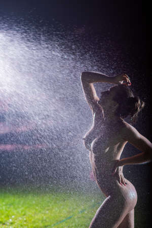 A beautiful European woman stands on a lawn under sprinkler at night. Flashes illuminate a girl without clothes in drops of water lawn splashes. Stock Photo