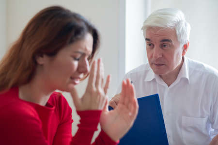 A woman cries during a psychotherapy session. Stock Photo