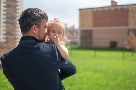 Loving father holds on hands of his little daughter outdoors.