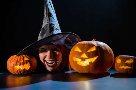 The head of an evil witch is on the table next to the glowing pumpkin jack-o-lantern