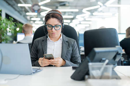 Business woman dressed in a headset is bored and uses a smartphone while sitting at a desk. Female manager is distracted from work by phone