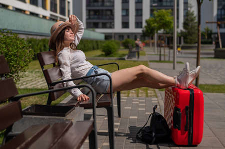 A beautiful young woman is sitting on a bench and put her legs on a red suitcase ouydoors Stock fotó